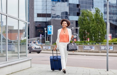 happy young african woman with travel bag in city