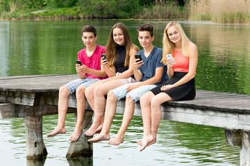 Vier Teenager / Jugendliche mit Smartphone draußen in der Natur
