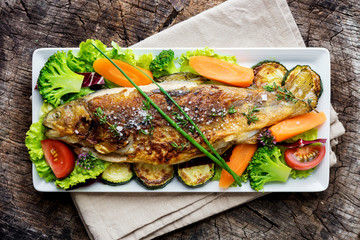 Grilled trout with vegetables on wooden background