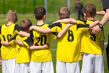 Young sport team with coach on sports field. Football; soccer; handball; volleyball; match for children. Youth sports team standing together. football soccer game. team work and penalty kick