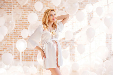 Beautiful and happy pregnant woman posing in a studio with balloons on a brick wall background