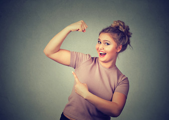 young happy woman flexing muscles showing her strength. Weight loss concept