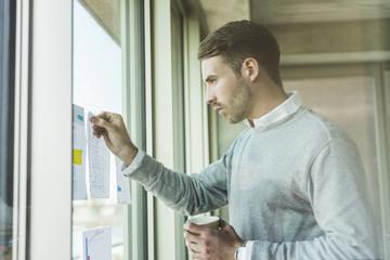 Geschäftsmann,Fensterscheibe,Fenster,Papier,schauen,Kaffee,Büro
