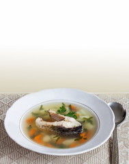 plate with carp fish soup and vegetables. sliced carp, potatoes, carrot, herbs. copy space, soft focus