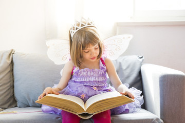 Portrait of little girl dressed up as fairy queen reading book