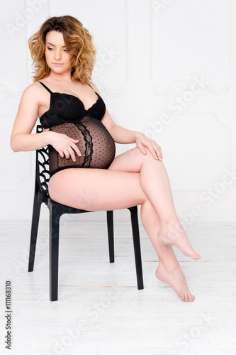 848352845 Young pregnant woman wearing lace lingerie in white interior. Fashion shot.