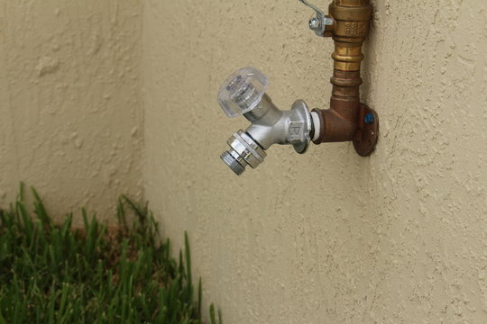 a water spigot on the side of a wall