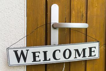 Welcome Schild hängt an Tür