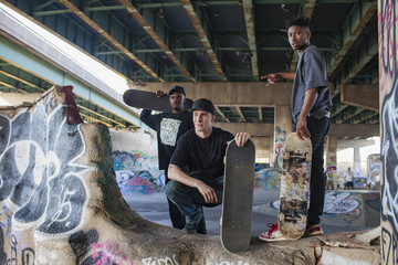 Three young men at a skateboard park.