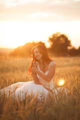 Happy beautiful young bride outside on a summer meadow at the sunset