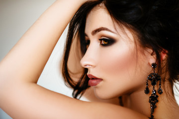 Soft focus. Portrait of a beautiful brunette girl with long hair, hair and makeup. Posing shows massive earrings