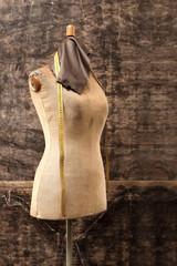 Manekin krawiecki. Kawałek skóry licowej, centymetr krawiecki upięty na manekinie w pracowni futer