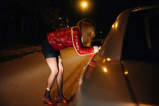 Street prostitute talking to potential customer in the car