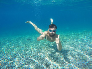 Beard man with mask diving in a blue clean water
