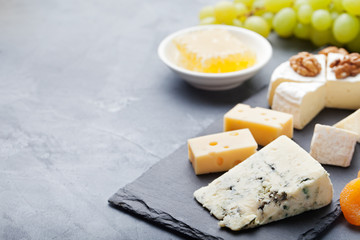 Glass of white wine and assorted cheese with grape on a stone and slate background.