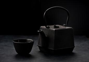 Asian cast iron tea set. Cast iron teapot and bowl, black grunge background