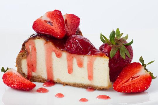 Slice cheesecake with fresh strawberries on white plate