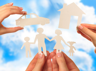 Hand holding a paper home, car, family on blue sky background