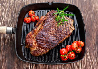 Grilled Beef Sirloin Steak on iron pan with vegetables.