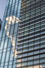 Immagini, cielo e nuvole bianche riflessi nella facciata a vetro  di un grattacielo