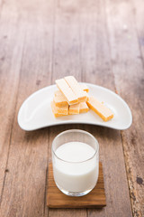 Glass of milk with waffles  on wooden