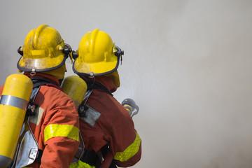 2 firemen spraying water in fire and smoke