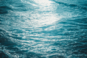 Blue waves of the sea and foam background, reflections of sun light