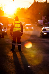 Police officer observe busy traffic. Sunset light with sun flare