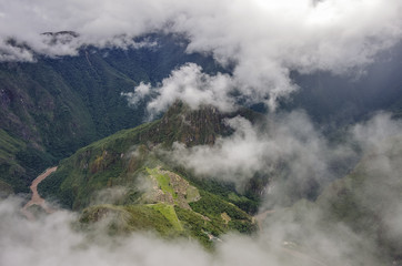 View of the Lost Incan City of Machu Picchu and Huayna Picchu mountain from Machu Picchu mountain .Low clouds .Cusco Region,Sacred Valley, Peru