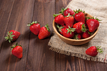 Fresh strawberries on an old wooden surface.
