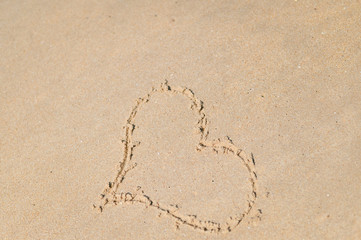 Top view on heart drawn in the sand. Beach background.