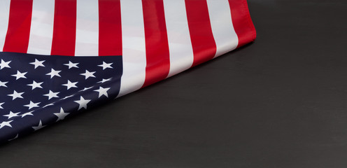 Folded American flag on black chalkboard with copy space