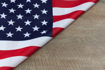 fragment of USA flag folded on wooden walnut table with copy space