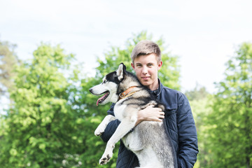 Owner and Siberian husky. Young guy holds on his hands of the Siberian Husky in the park.