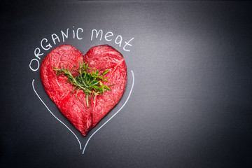 Organic meat for healthy Eating. Heart shape raw meat with herbs and text on black blank chalkboard background, top view