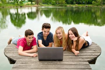 Gruppe Teenager mit Notebook draußen in der Natur