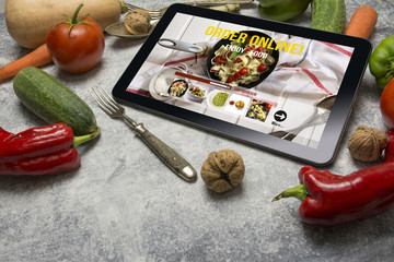 Tablet with Online food delivery app on screen. lifestyle concep