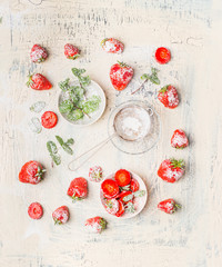 Flat lay of strawberries , powdered sugar and  mint leaves on white shabby chic wooden background, top view