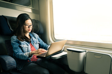 Asian woman work on laptop on train, business travel concept, warm light tone