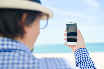 Back view shot of person holding using smartphone on beach background outdoors