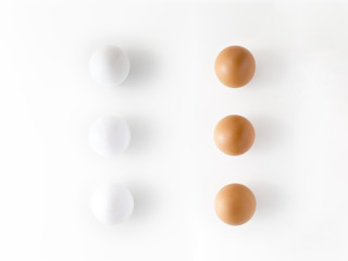 Top view of three white eggs and three brown eggs isolated on white