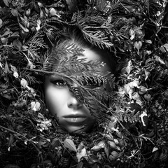 Fairy tale girl portrait surrounded with natural plants and flowers.Black-white art image in fantasy stylization.