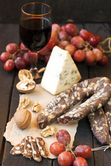 Snacks for wine, cheese with mold, pink grapes, walnuts