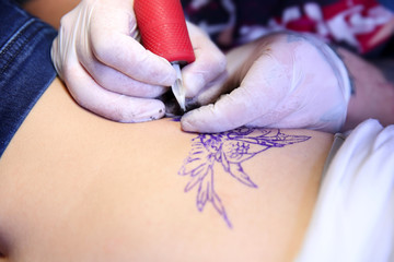 Master doing tattoo on female  body, closeup