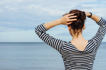 Woman in striped t-shirt and with curly hair looking at the sea