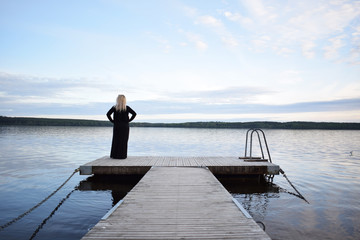 Young blonde woman with beautiful swedish landscape in the background