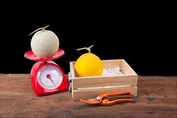 melon in wooden box ,melon on weighing scale, Scissors, isolate black backgorund