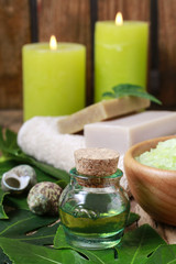 Bottle of green essential oil and scented candles