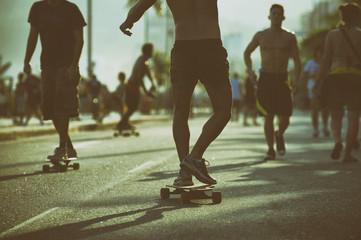 Brazilian skaters skate along the Ipanema Beach beachfront road in a toned scene in Rio de Janeiro, Brazil