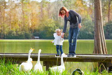 Kid girl and mother playing with ducks in lake